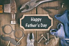 Happy Fathers Day chalkboard tag with tool, gift and tie frame on wood Royalty Free Stock Photos