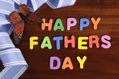 Happy Fathers Day childrens toy block colorful letters spelling greeting. On dark rustic wood table with blue ribbon and butterfly stock photography