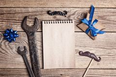 Happy fathers day concept. Blank notepad with spanners, gift and mustache on a wooden table. Large and small wrenches as a father. And son symbol. Copy space royalty free stock photo