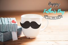 Happy fathers day concept. Gift box, mustache and coffee cup with paper red heart tag on wooden table background stock photos