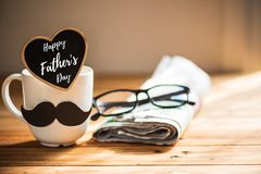 Happy fathers day concept. Coffee cup with black paper mustache, heart tag with Happy father`s day text and newspaper, glasses on wooden table background stock image