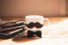 Happy fathers day concept. Coffee cup with black paper mustache and newspaper, note book, glasses on wooden table background royalty free stock photo