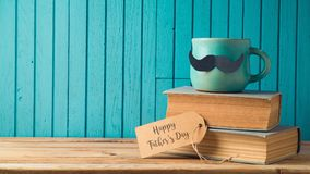 Happy Fathers day concept. With coffee cup, mustache and books over wooden background stock images