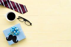 Happy fathers day concept. Red tie, glasses, mustache, gift box and coffee cup on bright yellow pastel wooden table background royalty free stock photos