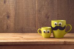 Happy Fathers day concept. With two coffee cups as father and son over wooden background royalty free stock image