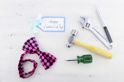 Happy Fathers Day concept with mens tools and pink bow tie. Royalty Free Stock Photos
