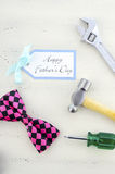 Happy Fathers Day concept with mens tools and pink bow tie. Royalty Free Stock Photography