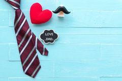 Happy fathers day concept. Red tie, handmade red heart mustache with LOVE DAD text on bright blue pastel wooden table background stock photos