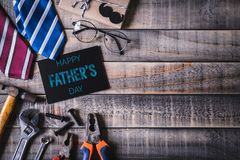 Happy fathers day concept. Top view of black paper tag with Happy father`s day text and left border of tools and ties, retro f stock images
