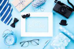 Happy fathers day concept. Top view of blue tie, beautiful gift box, alarm clock, white picture frame with Happy father`s day tex stock image