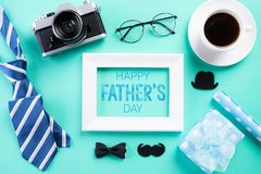 Happy fathers day concept. Top view of blue tie, beautiful gift box, black coffee cup, white picture frame with Happy father`s da stock images