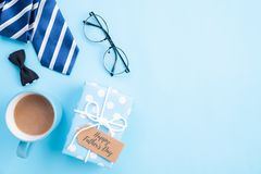 Happy fathers day concept. Top view of blue tie, beautiful gift box, coffee mug, glasses with LOVE DAD text on bright blue pastel stock photo