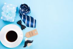 Happy fathers day concept. Top view of blue tie, beautiful gift box, coffee mug, paper tag with LOVE DAD text on bright blue stock image