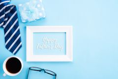 Happy fathers day concept. Top view of blue tie, beautiful gift box, coffee mug, white picture frame with happy father`s day text. On bright blue pastel stock images