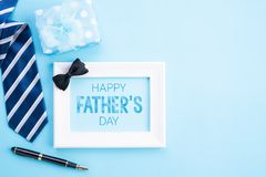 Happy fathers day concept. Top view of blue tie, beautiful gift box, coffee mug, white picture frame with happy father`s day text royalty free stock images