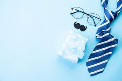 Happy fathers day concept. Top view of blue tie, beautiful gift box, glasses and mustache on bright blue pastel background. Flat stock photography