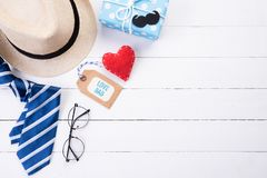 Happy fathers day concept. Top view of blue tie, beautiful gift box, man hat with glasses and retro film camera on white wooden. Table background. Flat lay royalty free stock photography
