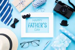 Happy fathers day concept. Top view of blue tie, beautiful gift box, man hat, white picture frame with Happy father`s day text an. D retro film camera on bright stock photo