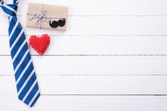 Happy fathers day concept. Top view of blue tie, beautiful gift box, red heart with man mustache on white wooden table background. Flat lay royalty free stock images