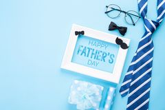 Happy fathers day concept. Top view of blue tie, beautiful gift box, white picture frame with Happy father`s day text on bright. Blue pastel background. Flat stock photos