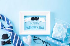 Happy fathers day concept. Top view of blue tie, beautiful gift box, white picture frame with Happy father`s day text on bright. Blue pastel background. Flat royalty free stock photo
