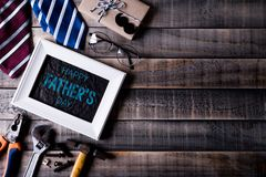 Happy fathers day concept. Top view of white picture frame with border of tools and ties, retro f glasses on dark wooden table. Background. Flat lay stock photo