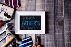 Happy fathers day concept. Top view of white picture frame with border of tools and ties, retro f glasses on dark wooden table. Background. Flat lay stock photos
