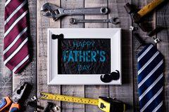 Happy fathers day concept. Top view of white picture frame with border of tools and ties, retro f glasses on dark wooden table. Background. Flat lay royalty free stock images