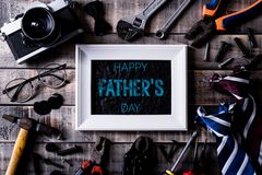 Happy fathers day concept. Top view of white picture frame with border of tools and ties, retro film camera on dark wooden table. Background. Flat lay royalty free stock photos