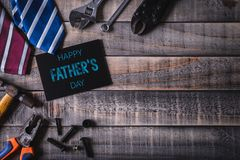 Happy fathers day concept. Top view of white picture frame with border of tools and ties, retro film camera on dark wooden table. Background. Flat lay stock image