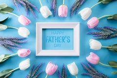 Happy fathers day concept. Top view of white pink tulip flowers and picture frame with Happy father`s day text on bright blue. Pastel background. Flat lay royalty free stock photography