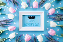 Happy fathers day concept. Top view of white pink tulip flowers and picture frame with Happy father`s day text on bright blue. Pastel background. Flat lay royalty free stock images