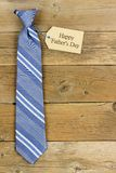 Happy Fathers Day gift tag with blue tie on wood Stock Photography