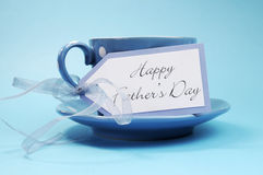 Happy Fathers Day gift tag with a cup of coffee or tea for Dad. In a blue polka dot cup and saucer against a blue background stock images