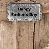 Happy Fathers Day on hanging metal sign against wood. Happy Fathers Day message on hanging metal sign against a rustic wooden background Royalty Free Stock Image
