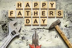 Happy Fathers Day inscription on wooden cubes with working tools on an old vintage concrete wall. Happy Father`s Day Concept. Gre. Etings and gifts. Holidays royalty free stock images