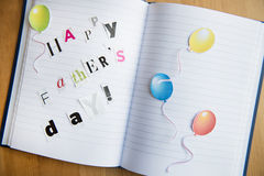 Happy Fathers Day. Letters Cut out from Magazine laying on the Notebook royalty free stock photos