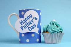Happy Fathers Day message on blue theme polka dot coffee mug with cupcake. Happy Fathers Day special treat blue and white beautiful decorated cupcakes with stock photography