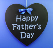 Happy Fathers Day message written on a heart shape black blackboard. With blue ribbon against a blue background stock photo