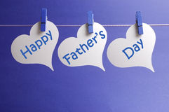 Happy Fathers Day message written on white heart shape tags hanging from blue pegs on a line. Against a blue background royalty free stock photo