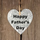 Happy Fathers Day metal heart, hanging over rustic wood. Happy Fathers Day metal heart, hanging over a rustic wooden background stock photo