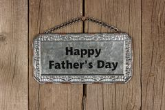 Happy Fathers Day metal sign against rustic wood. Happy Fathers Day message on hanging metal sign on a rustic wooden background Stock Photography