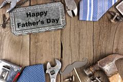 Happy Fathers Day metal sign with double border on wood. Happy Fathers Day message on a metal sign with double border of tools and ties on a wooden background Royalty Free Stock Image