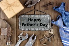 Happy Fathers Day metal sign with tool, gift and tie frame on wood. Happy Fathers Day message on metal sign with frame of tools, gifts and ties on a wooden Royalty Free Stock Photo