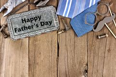 Happy Fathers Day metal sign with top border on wood. Happy Fathers Day message on metal sign with top border of tools and ties on a wooden background Royalty Free Stock Photos