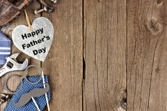 Happy Fathers Day metallic heart with side border on wood. Happy Fathers Day metallic heart with side border of tools and ties on a wooden background Royalty Free Stock Photos