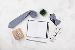 Happy Fathers Day mockup with notebook, gift, glasses, necktie and bowtie on white background top view in flat lay style. Royalty Free Stock Images