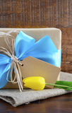 Happy Fathers Day Natural Kraft Paper Gift. Happy Fathers Day, or masculine birthday, natural kraft paper wrapped gift with pale blue ribbon on dark wood Stock Photos