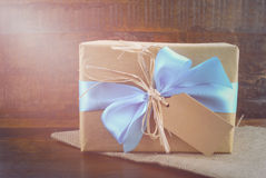 Happy Fathers Day Natural Kraft Paper Gift. Happy Fathers Day, or masculine birthday, natural kraft paper wrapped gift with pale blue ribbon on dark wood Stock Photo