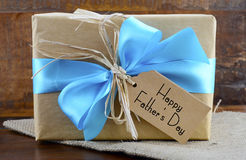 Happy Fathers Day Natural Kraft Paper Gift. Happy Fathers Day natural kraft paper wrapped gift owith pale blue ribbon on dark wood background stock photos